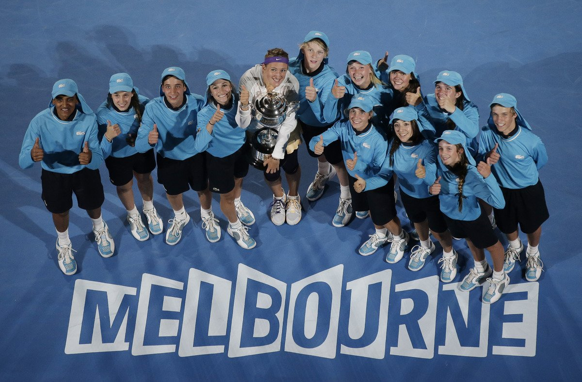 Victoria Azarenka holds her trophy as she stands amongst the ball boys and girls